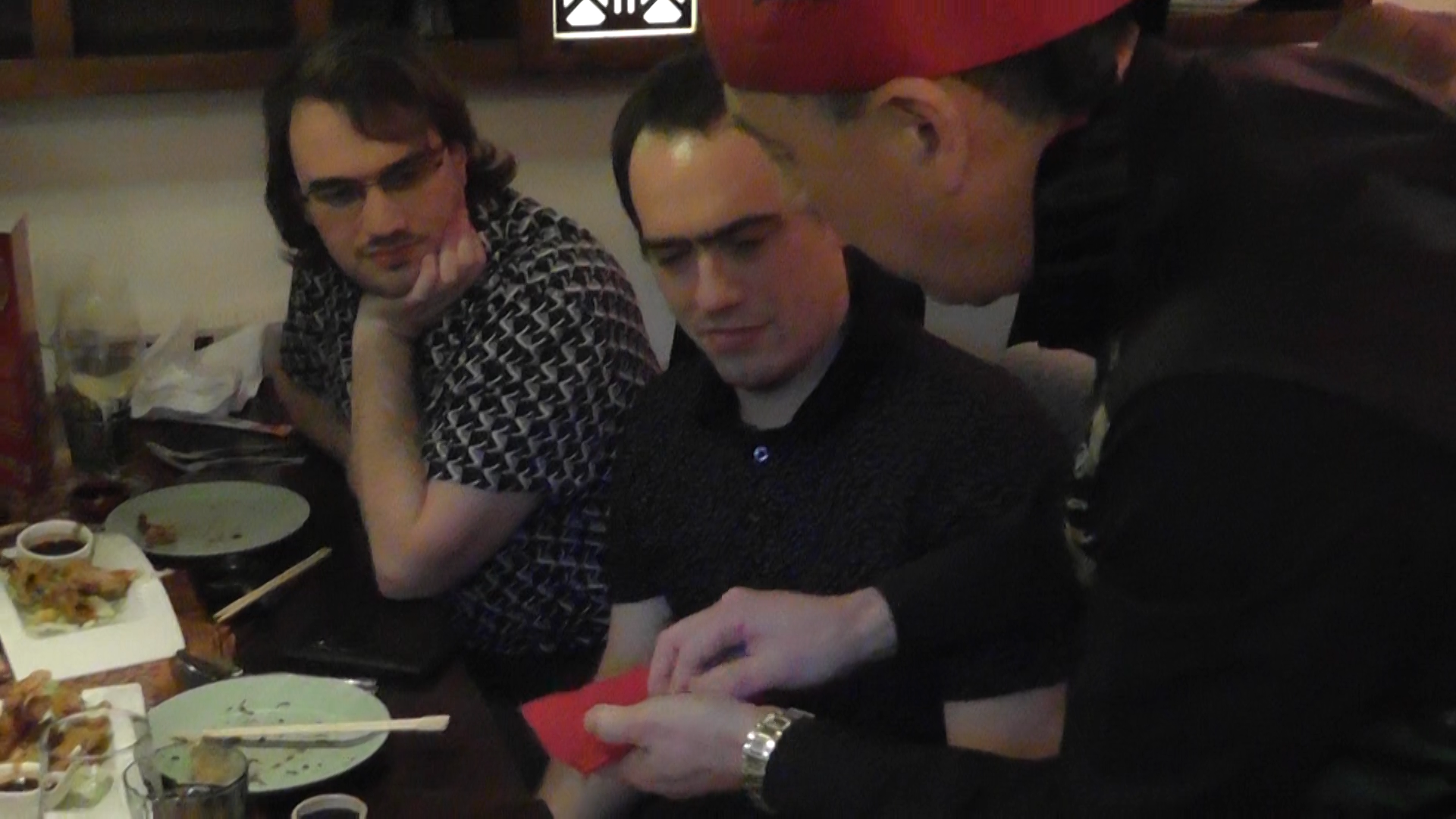 Table in restaurant with group of young people with disappearing coin trick